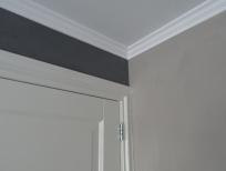 Detail spuitwerk plafond en schilderwerk sierlijst en deur
